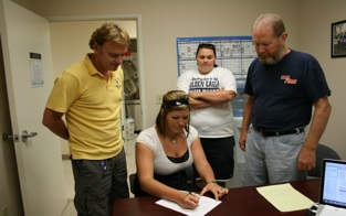 Coach Dani Bishop and others look on as Shawna McBride signs letter of intent